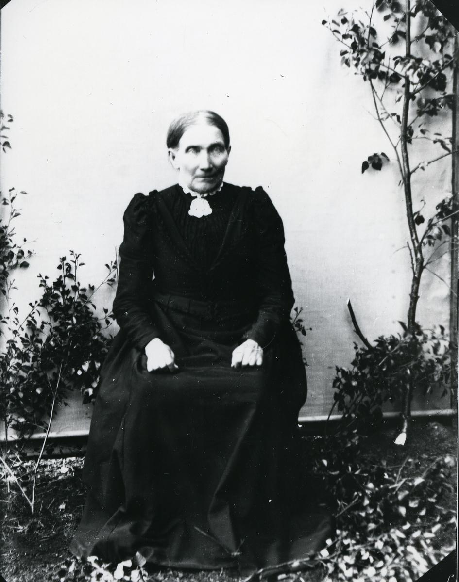 Eldre kvinne kledd i mørk kjole med sølje, sittende foran lerret
