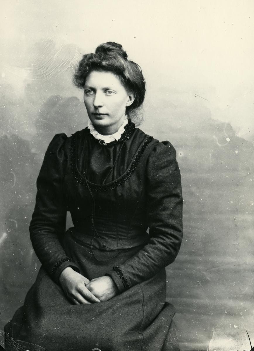 Kvinne, sittende foran lerret, fotografert i halvfigur
