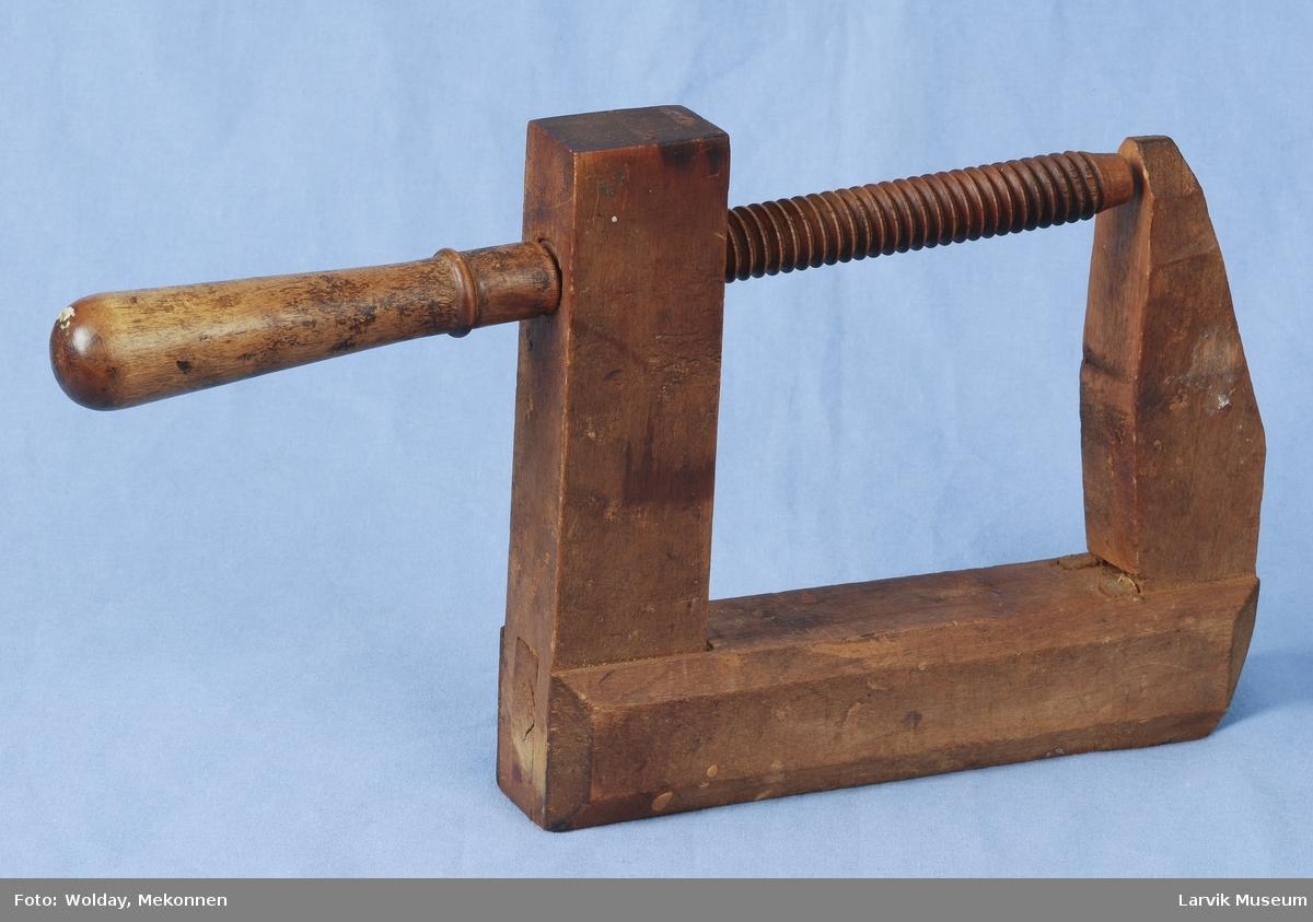 Form: Som en rettkantet C med hull i den nederste delen hvor det skrus inn en pinne med skruriller. Den øverste delen er noe kortere og spissere i enden.