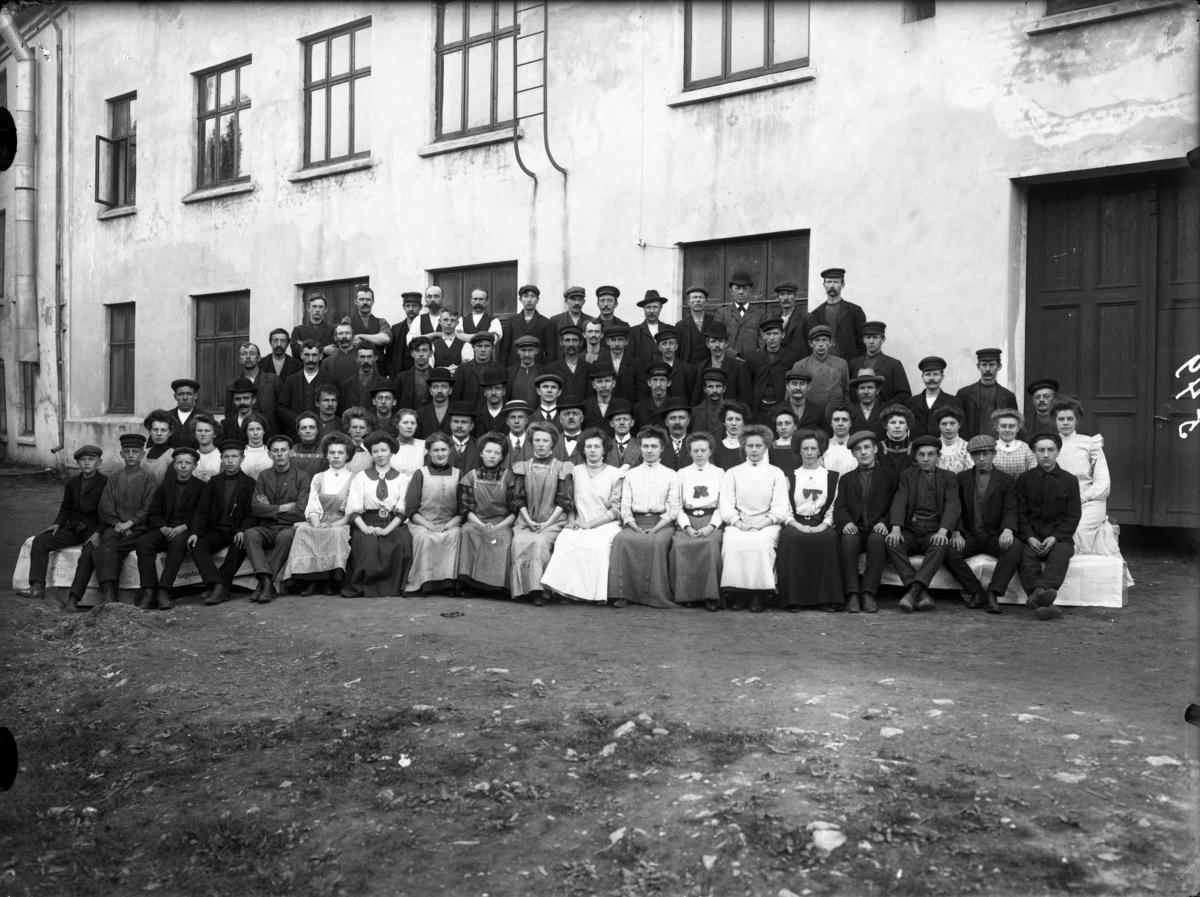 Utendørs gruppebilde. Arbeidere ved I. H. Becks sykkel- og konfeksjonsfabrikk i Kongens gate.
