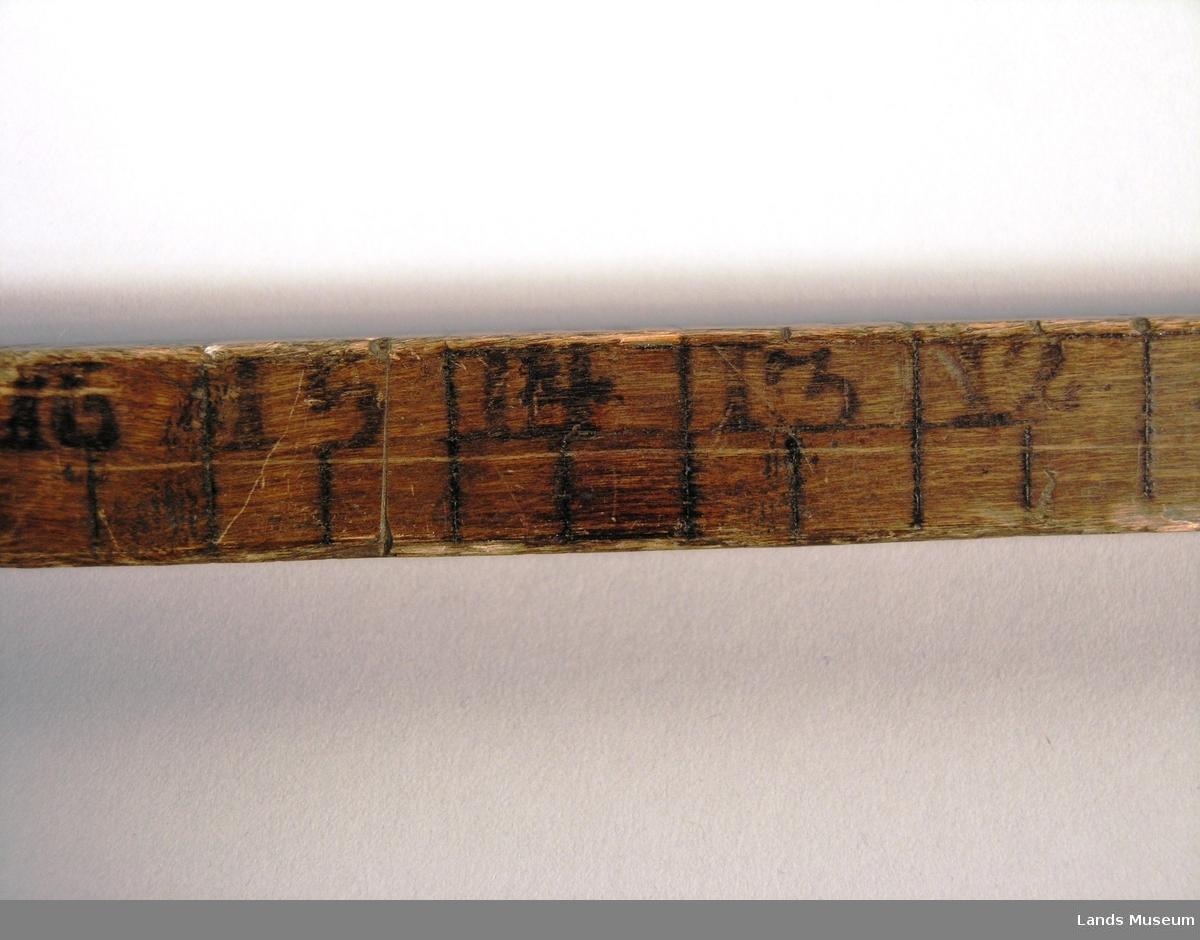 Delt opp i tommer på tre av sidane. Den fjerde sida er dekorert med namn og årstall. Namnet er utydleg, (initialer P. B. H.) 1824.