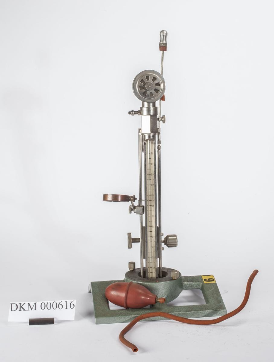 Måleinstrument med målesøyle av glass og vakumpumpe med slange. Rektangulært understell av metall som har en sirkel i midten hvor målesølen er montert.