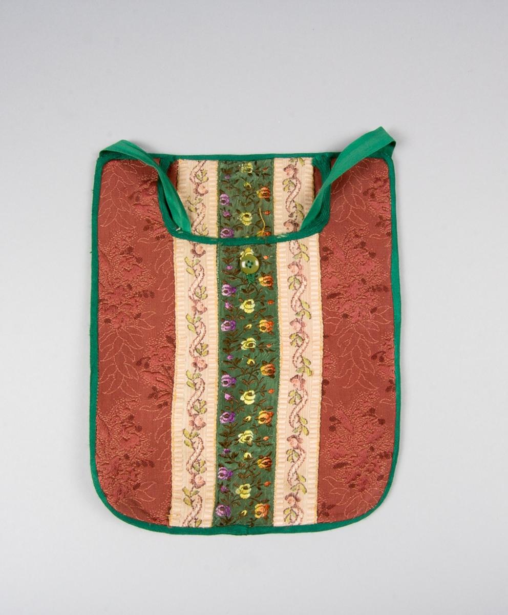 Kjolsäck till dräkt för kvinna från Västra Vingåkers socken, Södermanland. Modell med u-formad öppning. Tillverkad av brunrosa mönstervävt fabrikstillverkat bomullstyg. I mitten lodrätt två jacquardvävda bårder troligen klippta från ett tyg, med blomsterslinga i brunt, grönt och rosa på beige botten. Dessa flankerar ett bredare band, troligen av konstsilke med blommor i lila, gult och gulrött på grön botten. Strax under öppningen ett knapphål, sytt med grön tråd. Knappen är grönbrun. Kantat runtom med diagonalvävda gröna konstsilkeband. Framstycket ofodrat. Fabriksvävt linnetyg i tuskaft  har använts till bakstycke. Midjeband gröna, av bomull.
