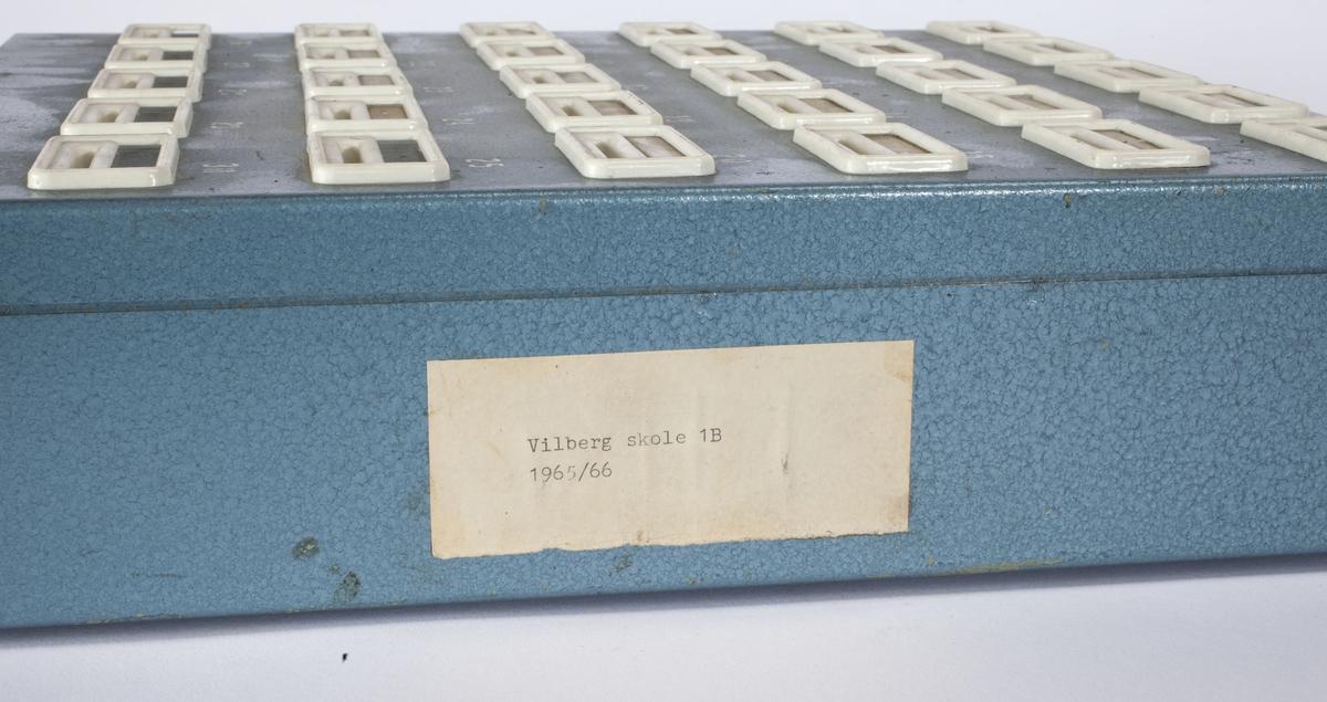 Rektangulær kasse med 30 rom. På fronten er det 30 sprekker til innkast av mynt, disse er nummerert fra 1 til 30 og har plass til navnelapper. Det er navnelapper over 24 av disse sprekkene.