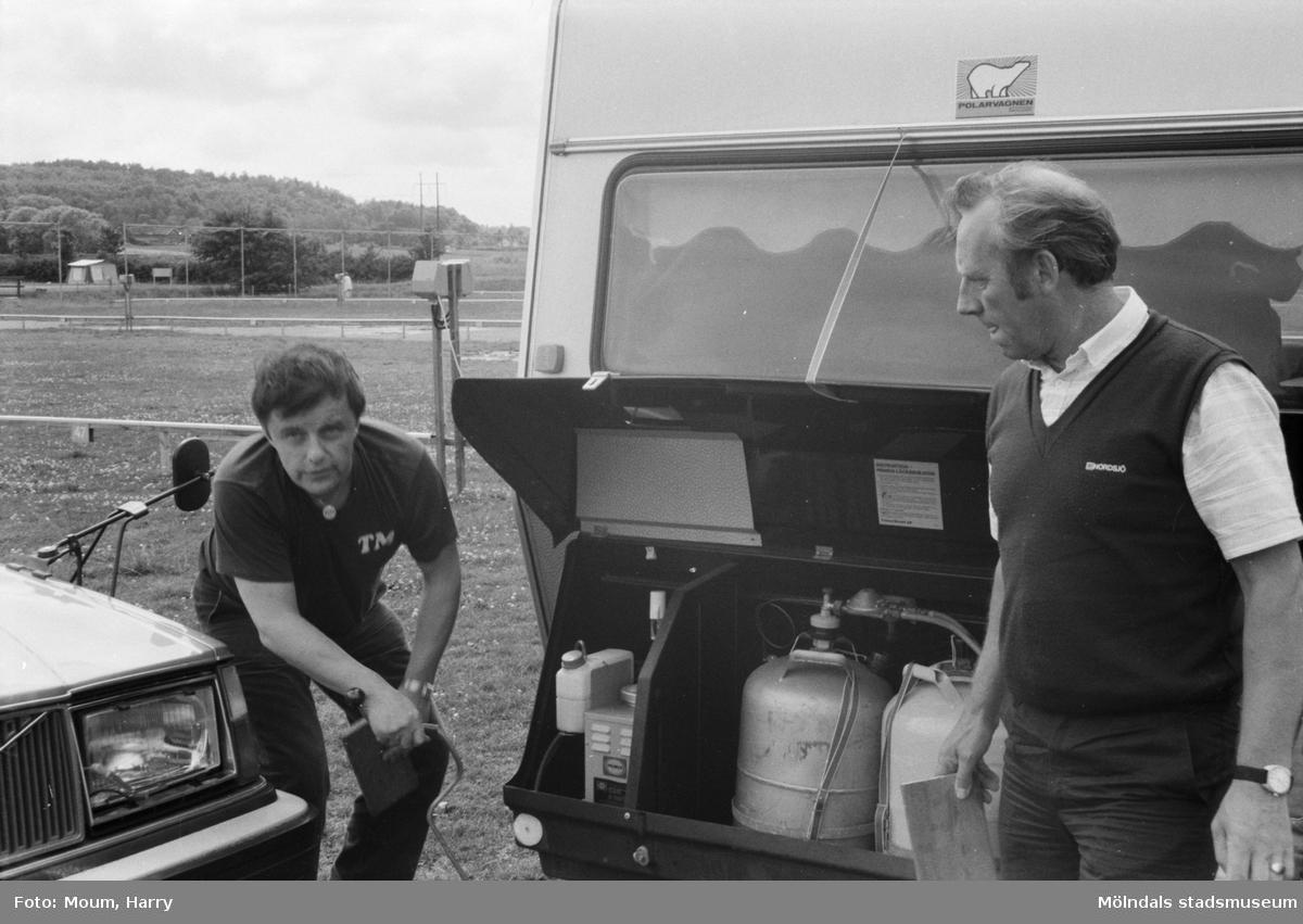 """Campare vid Åby camping i Mölndal, år 1984. """"- Vi håller på att greja med strömtillförsel, gasol och mat, skrattar äktaparen Mortensen från Tromsö och Myrbakk från Fredrikstad. - Och jag har gjort misstaget att kontakta mitt företag på första semesterdagen, säger Torbjörn Myrbakk. Affärsvänner från Japan väntar där hemma, så jag får ta första flyget till Norge och sedan via flyg försöka hinna ifatt de andra i Köpenhamn.""""  För mer information om bilden se under tilläggsinformation."""