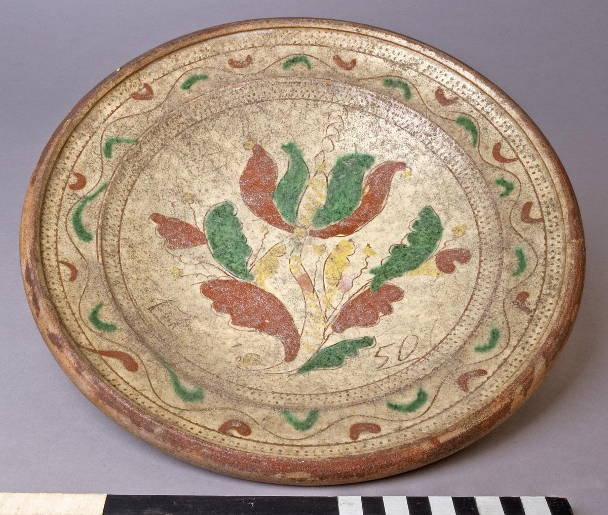 Fat av lergods. Dekorerat med engobe av vitgul piplera, skraffering, gulbrun, gul och grön glasyr. Brättet med våglinje, hemringen med skraffering, spegeln med blomstermotiv och årtalet: 1750. Undersidan oglaserad.