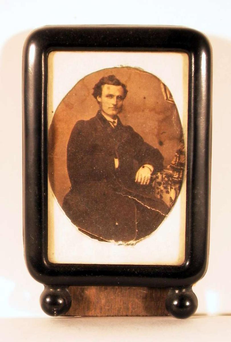 Portrett av yngre mann sittende ved bord og hvilende venstre arm på bordet og høyre hånd i jakken (à la Napoleon); han ser direkte på betrakteren.
