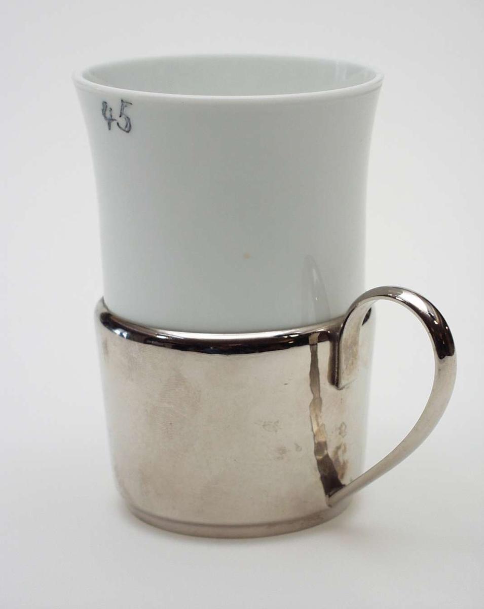 Hvit kopp i glass med matt overflate. Undestell i metall med hank.