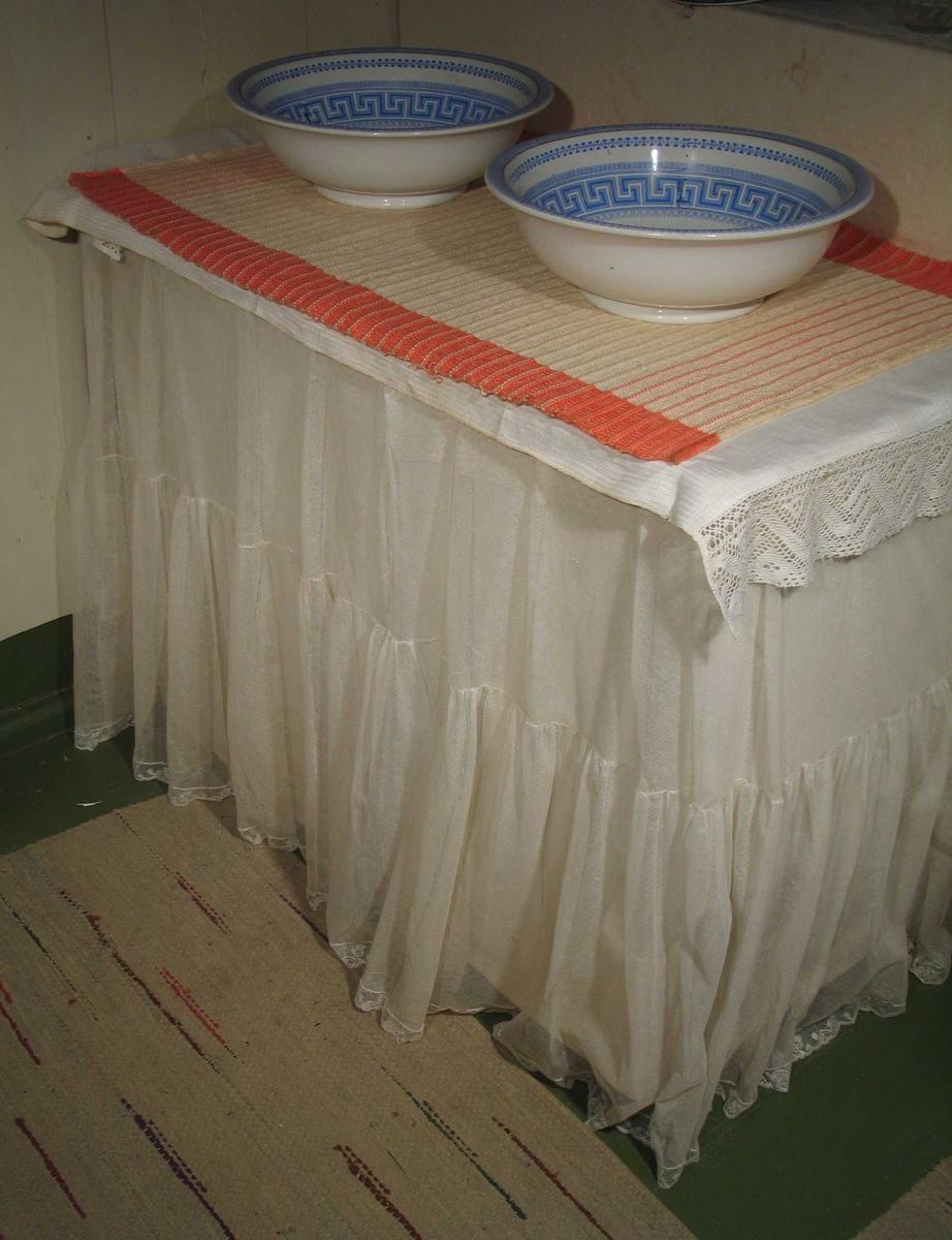 Forheng til toalettbordet sydd i hvit bobinette valencienneblonder. Det har en rynket kappe nederst. Forhenget er lagt i folder og festet til bordet med tegnestifter.
