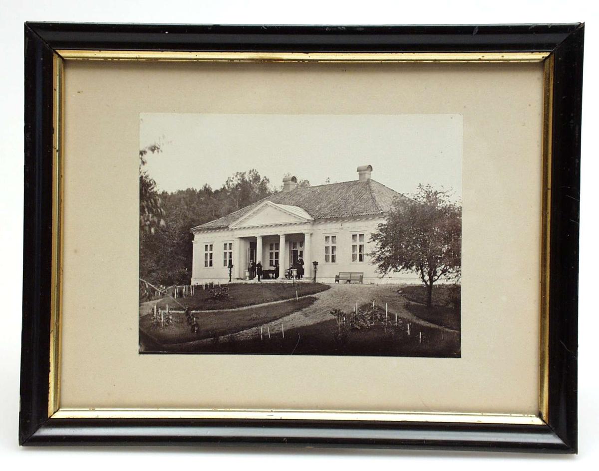 Fotografi innrammet i svart ramme med gullkant innerst.  Bakstykke av tre med innskrift.