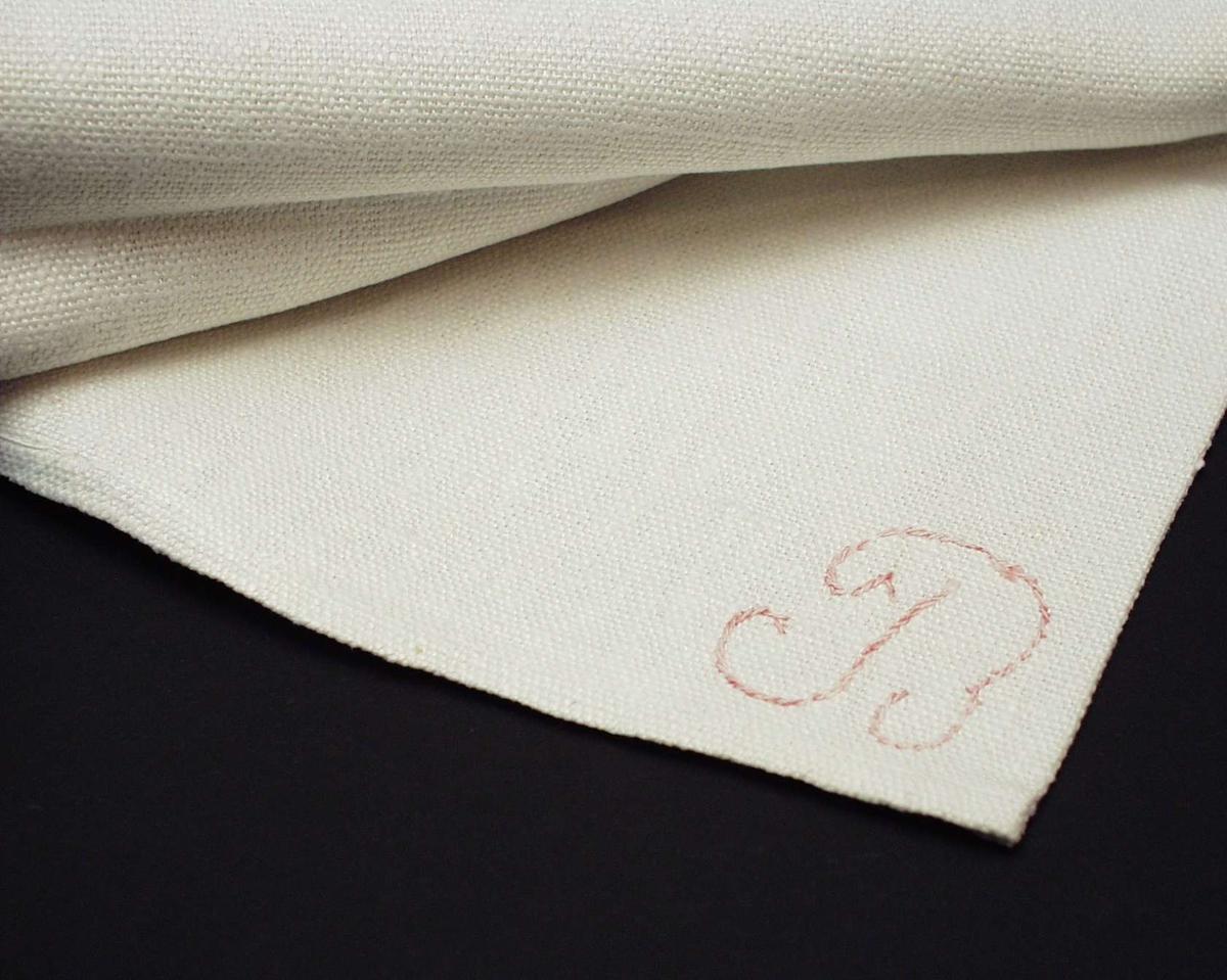 Halvbleket håndkle i lin med brodert monogram i rosa.