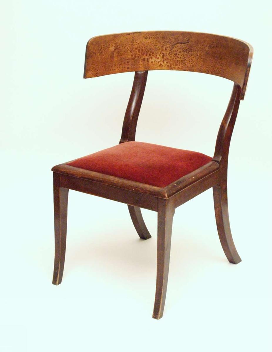Stol i bjørk med bøyd ryggbrett og rødt stoppet sete. Benene bak er mer svungne enn forbenene.