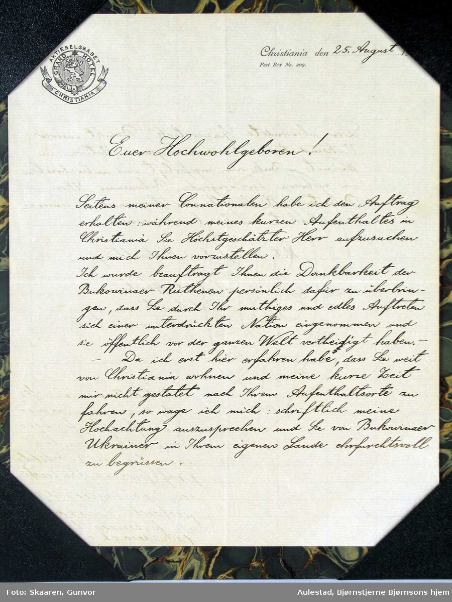 Håndskrevet brev satt inn i grønn marmorert pappramme.