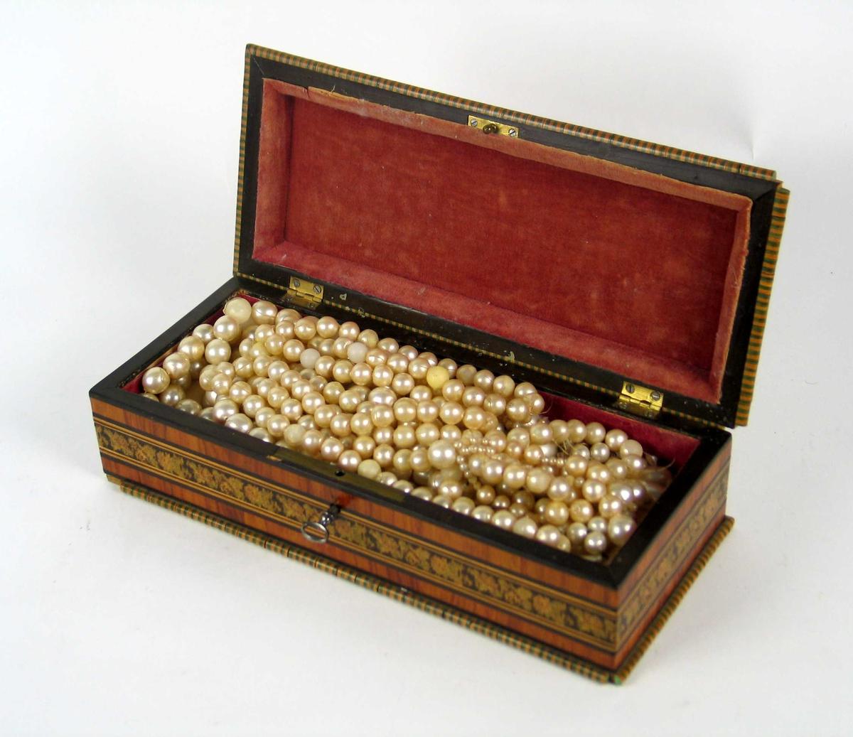 Skrin med intarsia. Lokket buer innover og har i oval et bilde av dansende figurer. Inneholder kjede med romerske perler, nål og hattenål.
