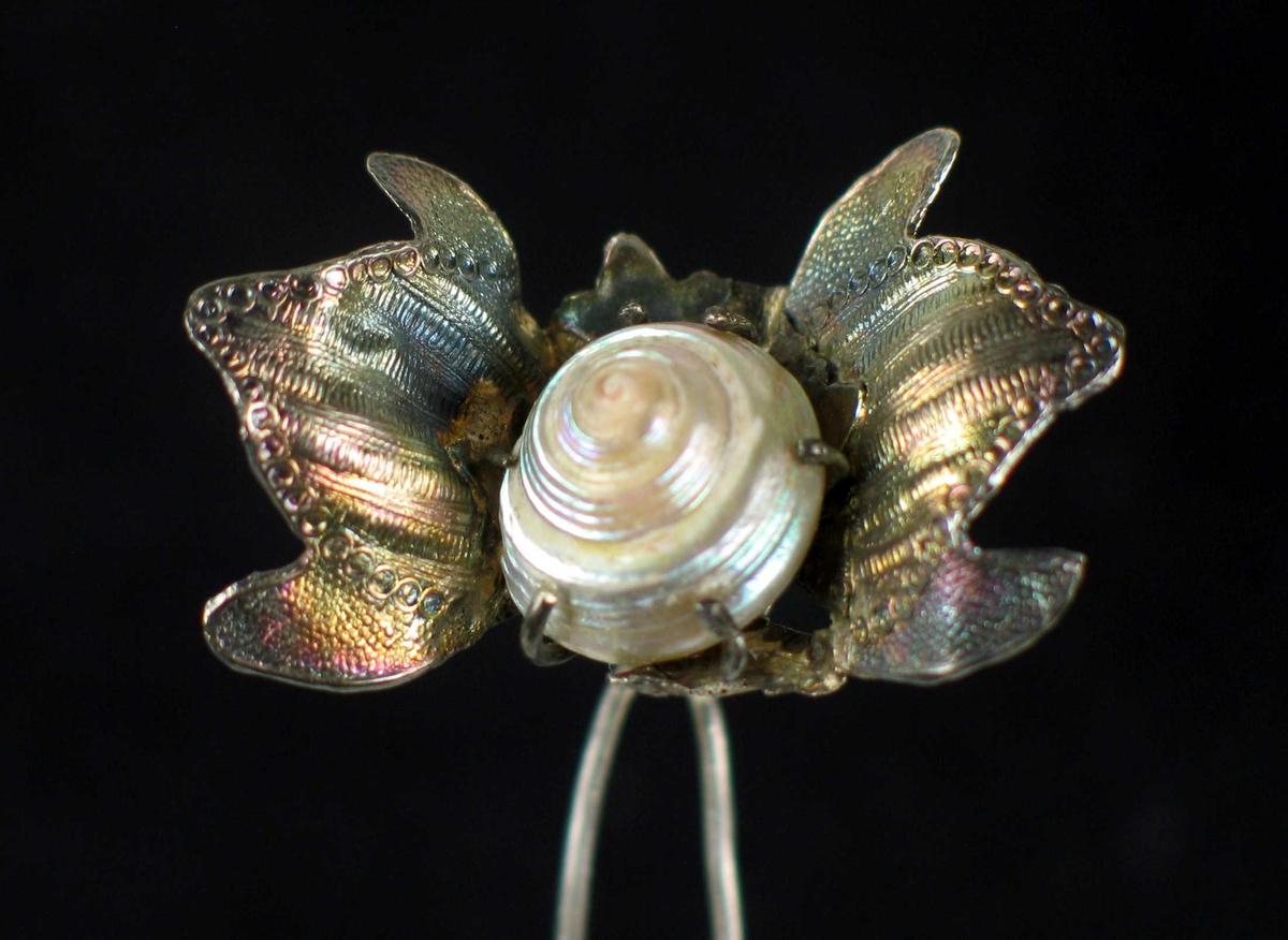 Hårpynt i sølv med to blad/vinger og innfattet sneglehus i midten. Påloddet lang hårnål.