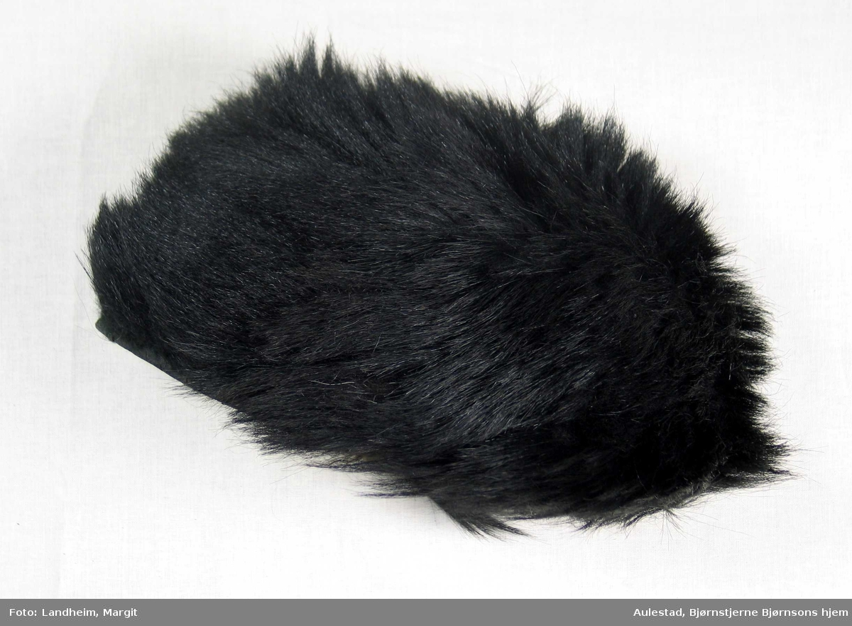 Lue i langhåret stri pels av ukjent type. Luen har et rundt issestykke og påsydd kant, 12 cm høy for luehøyde. Den har vattert, svart fôrsateng med rundt issestykke og kant, delt i to med to sømmer.