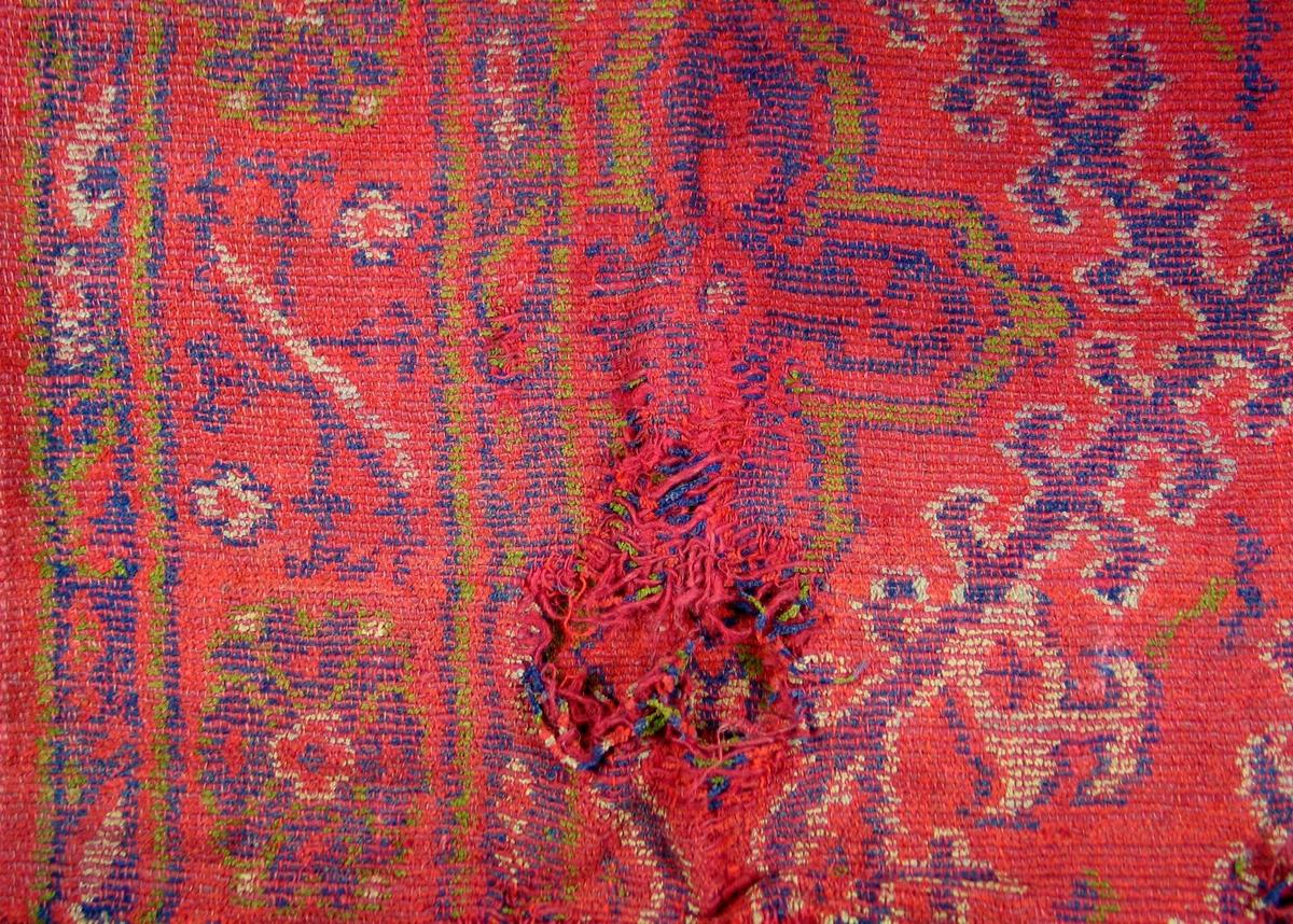 Golvteppe med rød bunnfarge og mønster i blått, grønt og hvitt. Innslaget er flosset tråd. Vevbredden er 170 cm. Faldet i kortsidene.