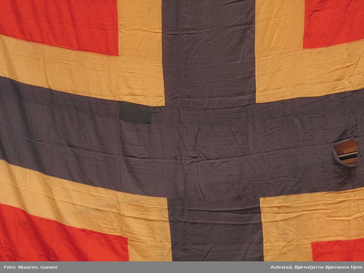 Stort norsk flagg lagt i folder og isydd ringer langs ene siden. Flagget er nesten kvadratisk. Det blå feltet har en bredde på 66, det hvite 34 og det røde 190 cm.