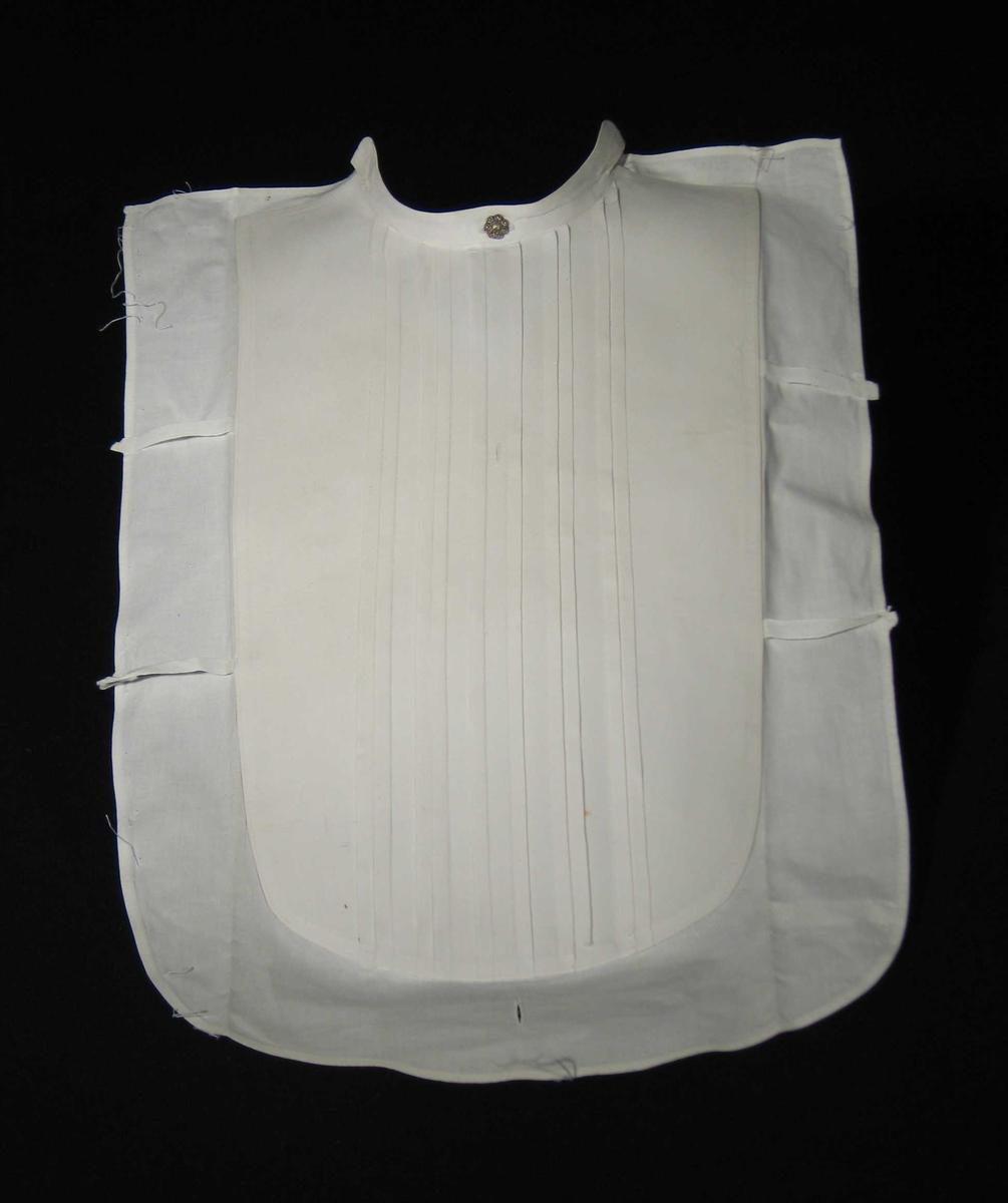 Hvitt stivet skjortebryst med metallknapp øverst, fem stukkede folder og hemper på sidene. Knapphull nederst.