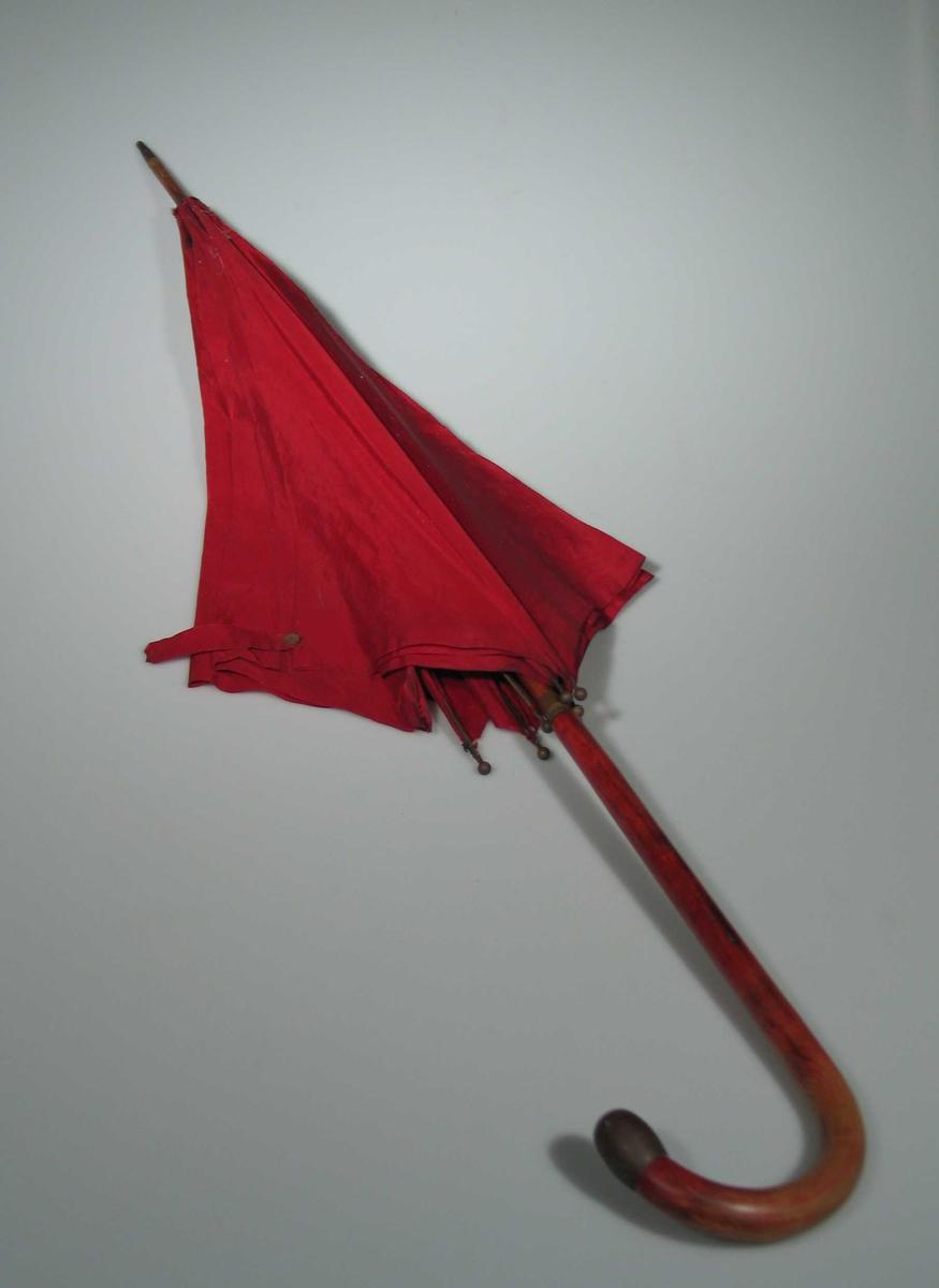 Paraplystang av tre med buet håndtak. Messingholk øverst og nederst og messinkule, ca 6 mm i diam på toppen av hver spile. Messing i låsmekanisme. Rød to-skaft silke i skjerm.