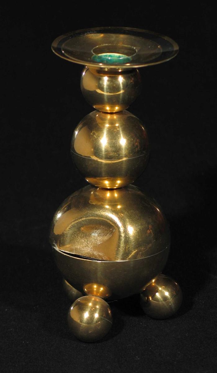 Lysestake i messing med tre runde fotknopper. Staken består av av stadig mindre kuler oppå hverandre. Fast mansjett.