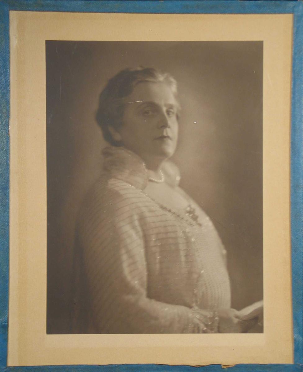 Fotografi limt på kartong og rammet inn med glass og blå shirting.