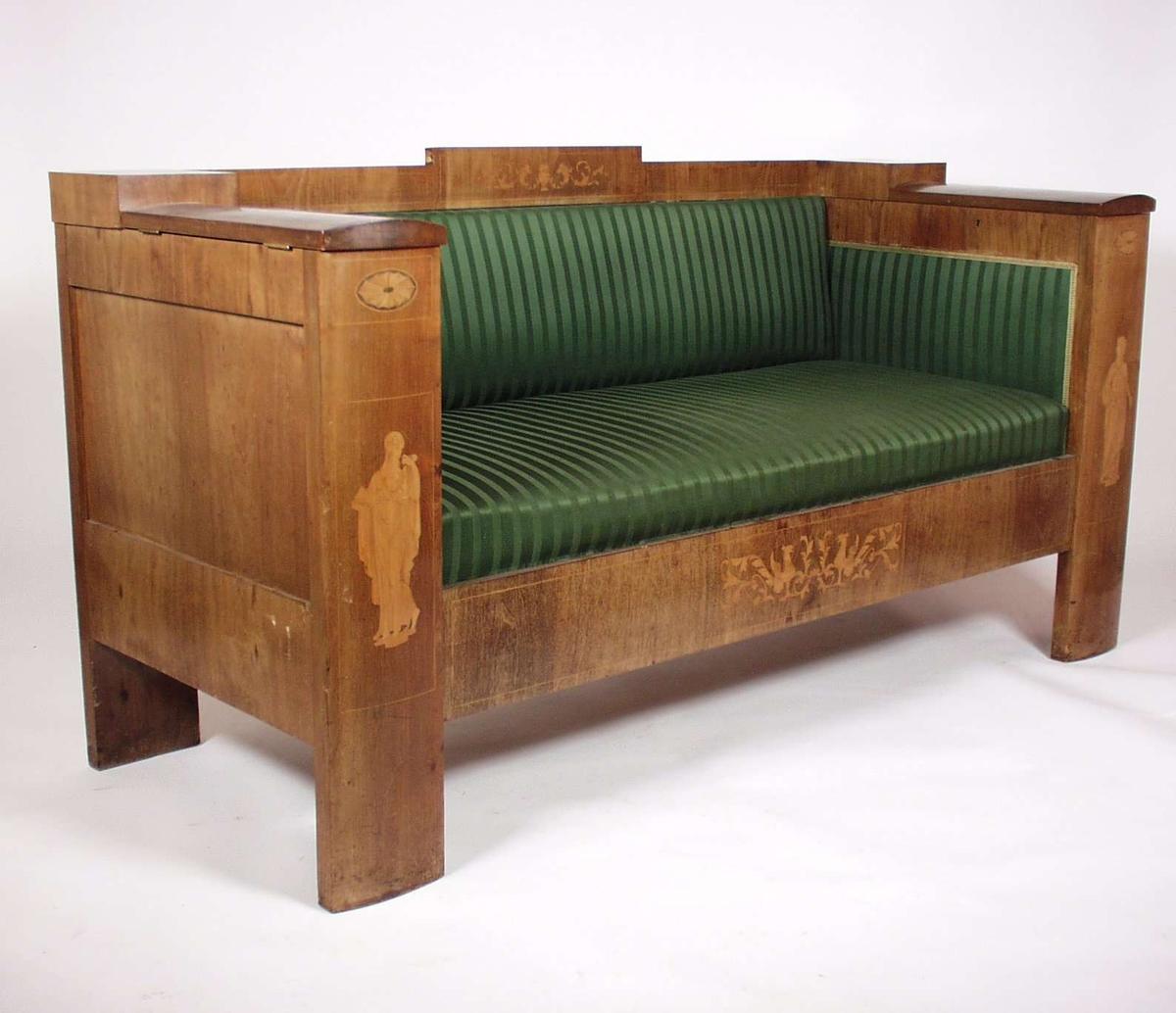 Sofaen er i tre med stoppet sete i grønt ullstoff. Sofaen har et lite rom i hvert armlene med nøkkel.To brikker ligger i det ene rommet.  Sofane har intarsiadekor  i sargen foran, på ryggstø og i front på armlenene.