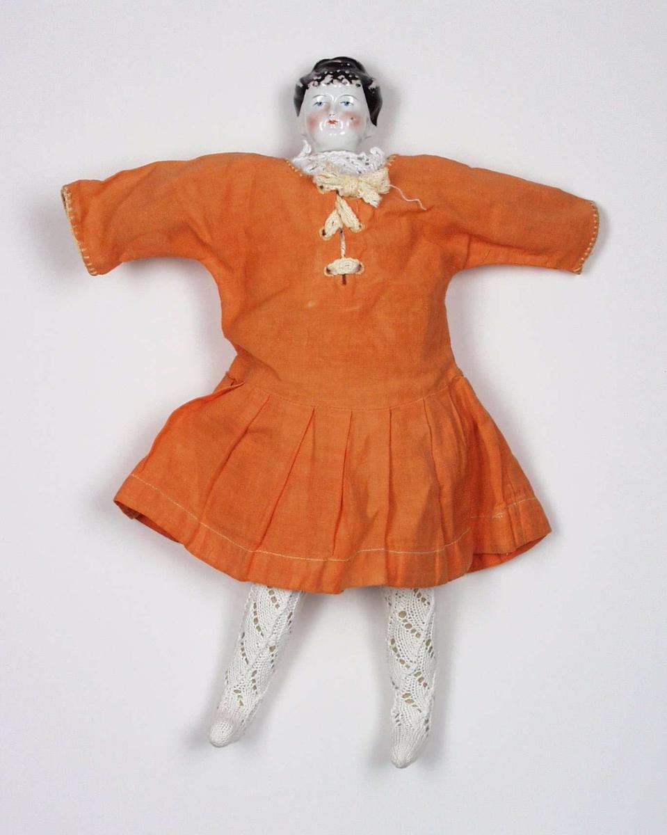 Dokka har porselenshode og hjemmelaget stoffkropp. Kjolen har snøring i halssplitten foran og  lavt liv med foldet skjørt. Strømper og trøye er i ensfarget mønsterstrikk.