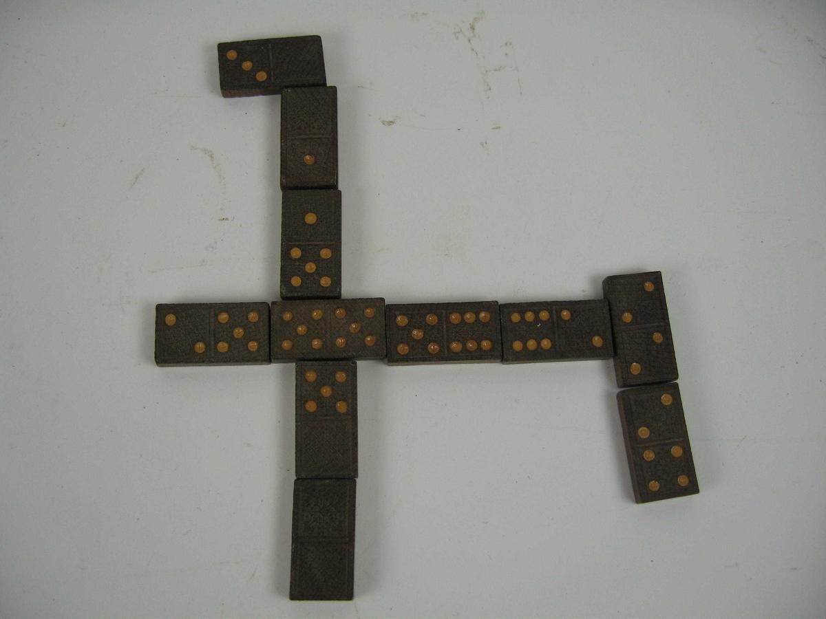 Et sett med 28 dominobrikker laget av en mørk tresort. Baksiden har et jugendmønster, mens på oversiden er nummereringen merket med oker fargeflekker.