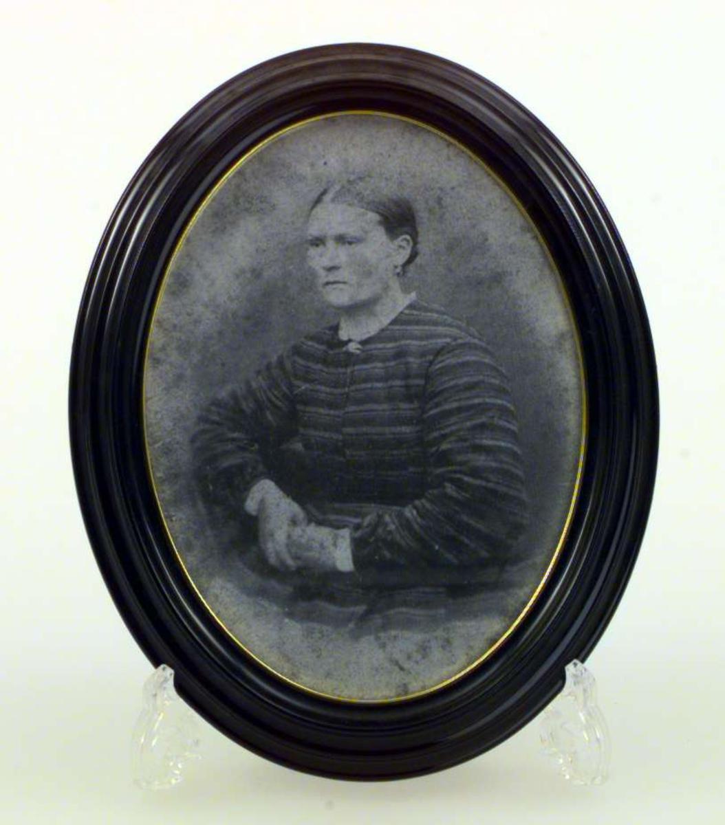 Utklippsbilde i oval sort ramme. Rammen har en forgyllet kant inn mot bildet.