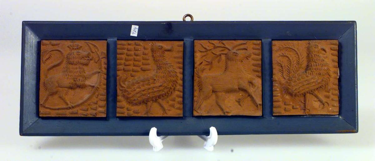 Fire avstøpninger i gips satt sammen i en treramme. Motivene er dyrefigurer - løve med krone, fugler, hjort.