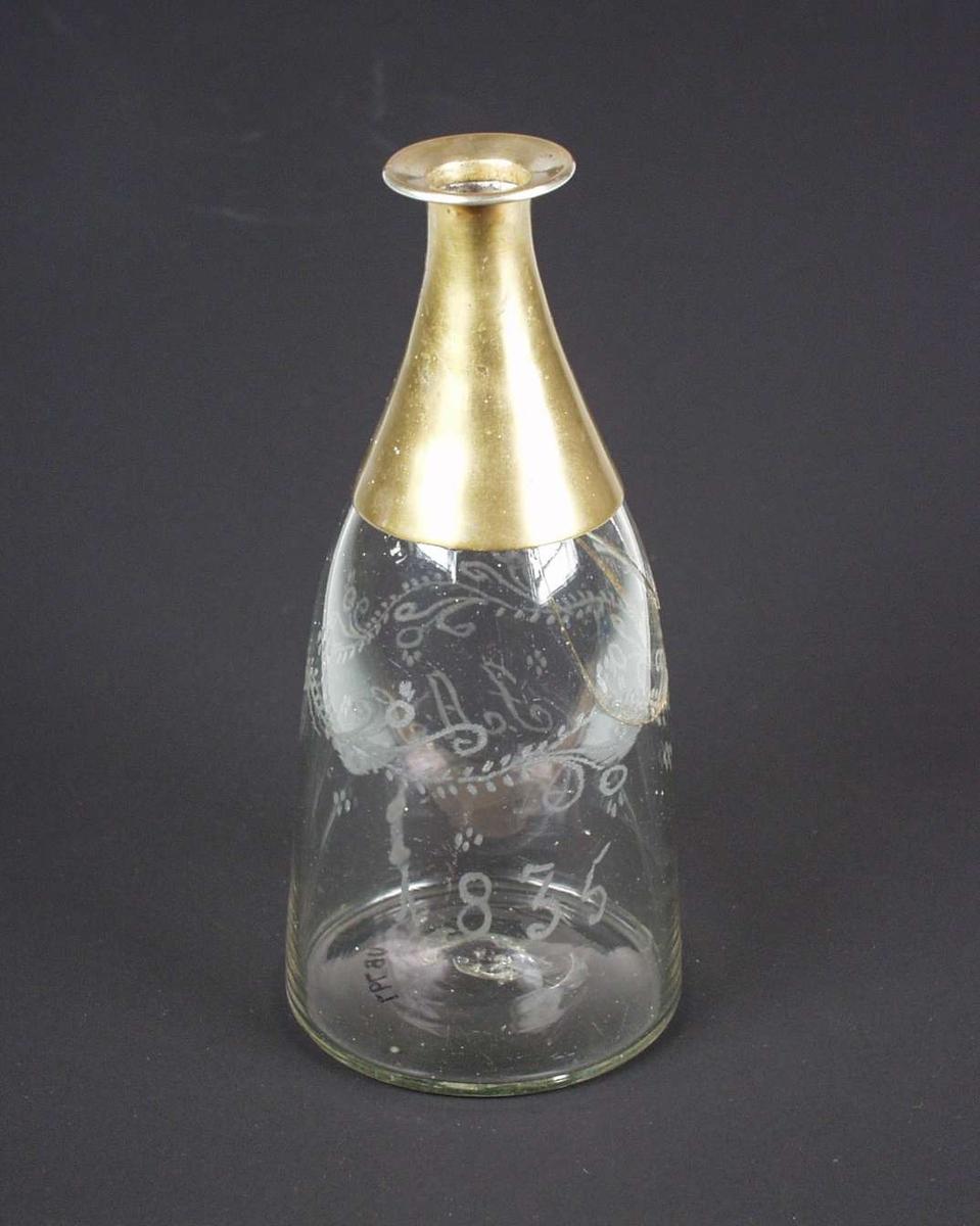 Stolbergs karaffel av klart glass med gravyr. Den har skrå skuldre og bred bunn, og den er dekorert med girlander. På en side er gravert 'J. A. S'., på baksiden '1835'.Karaffelen er defekt, den har påsatt hals av messing.