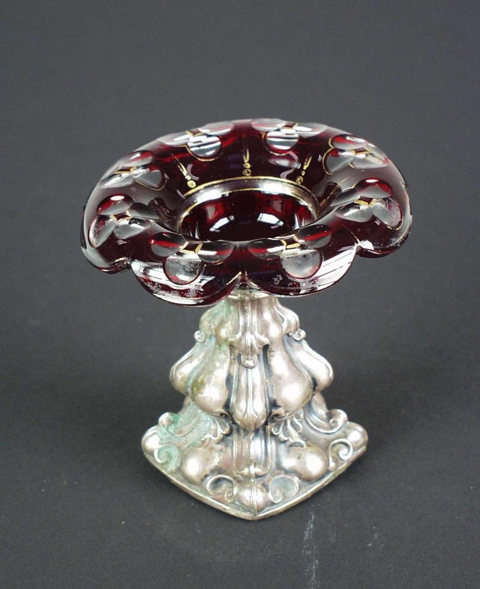 Saltkar med forarbeidet metallstett og glasskål med utbrettet kant. Rubinrødt overfangsglass, olivenslipt og med forgylt dekor.