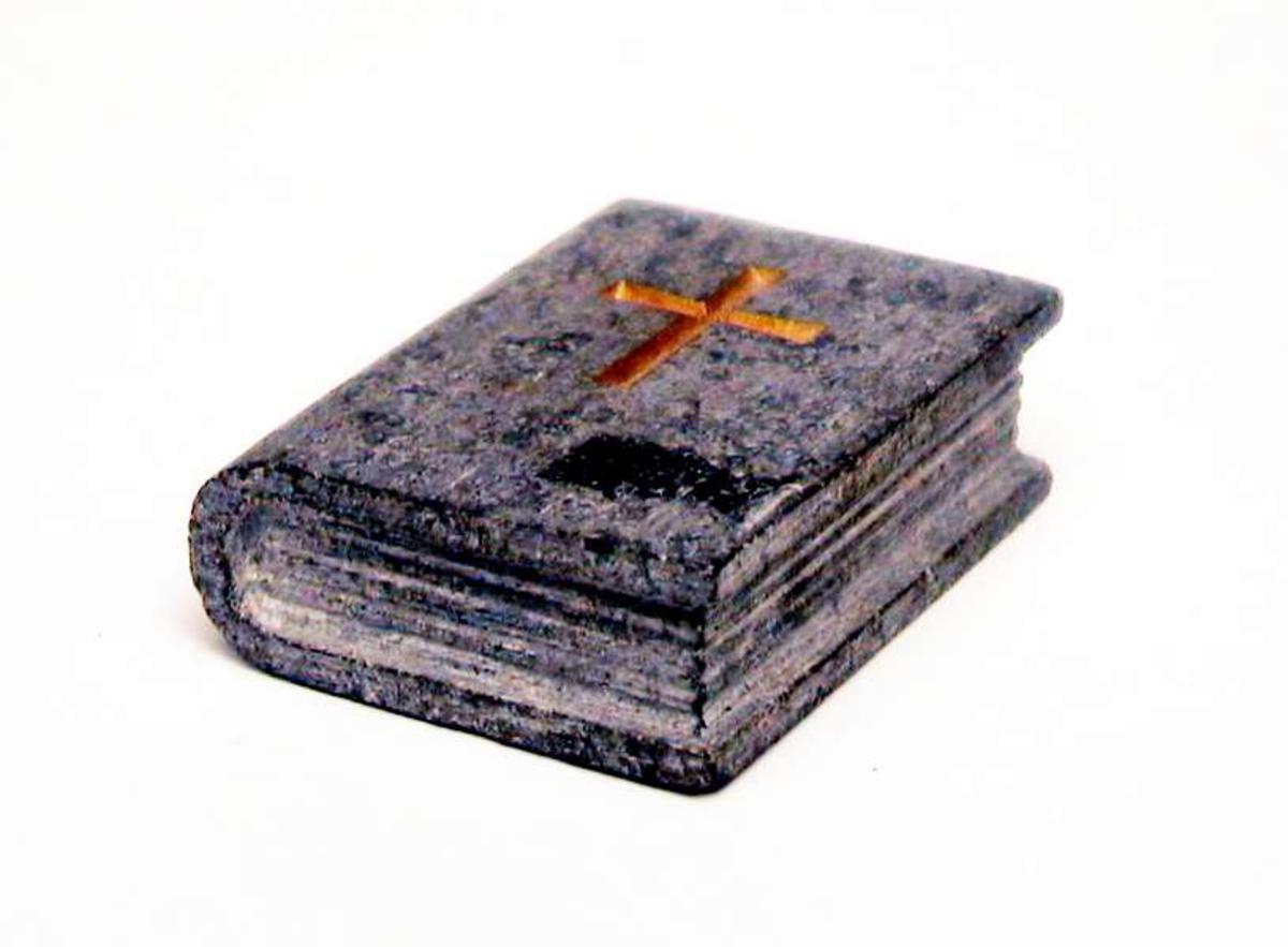 Liten bok laget av kleberstein. Den har et forgylt kors risset inn i permen.