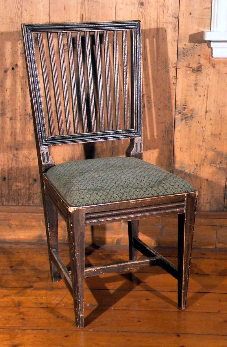 Spisestuestol med sprosser i ryggen og med stoppet sete. Stoffet i setet er grønt med takstensmønster. Trekket er flekket. Stolen er brunmalt, sprossene er malt røde og grønne. Malingen er delvis avslitt.