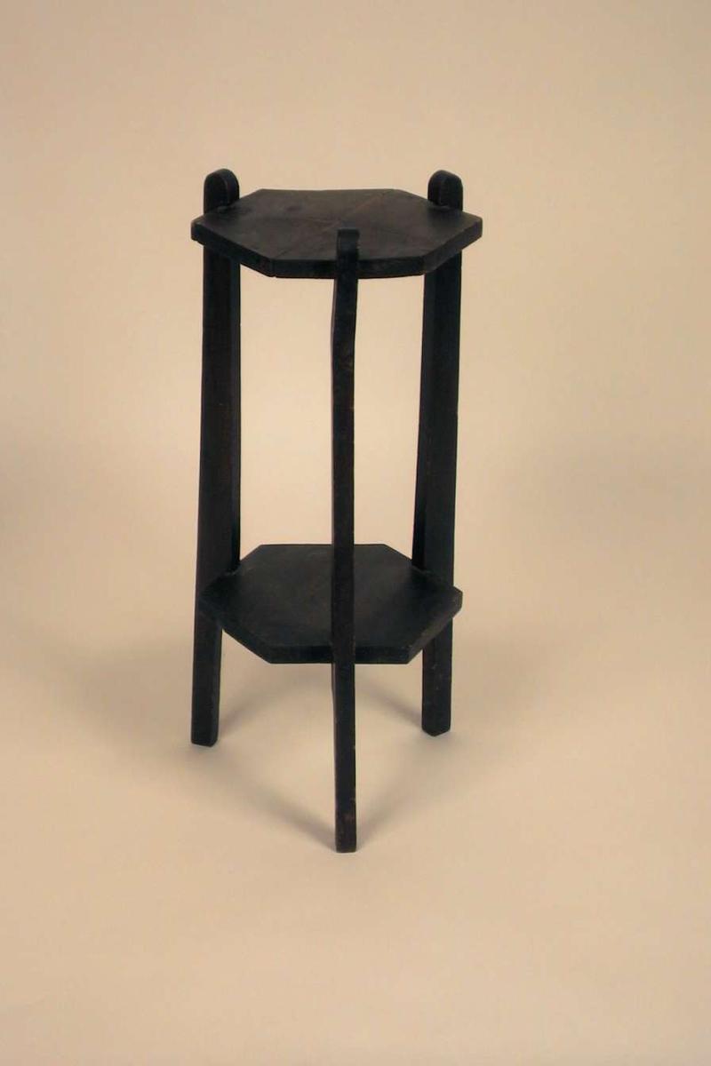 Lite blomsterbord på tre ben med hylle. Platen og hyllen er sekskantet.