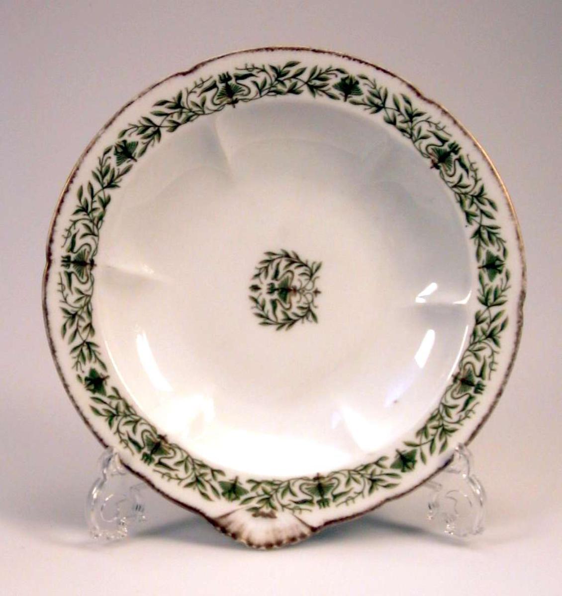 Fat i keramikk med hvit glasur og med dekor i  grønt. Kanten er forgyllet.