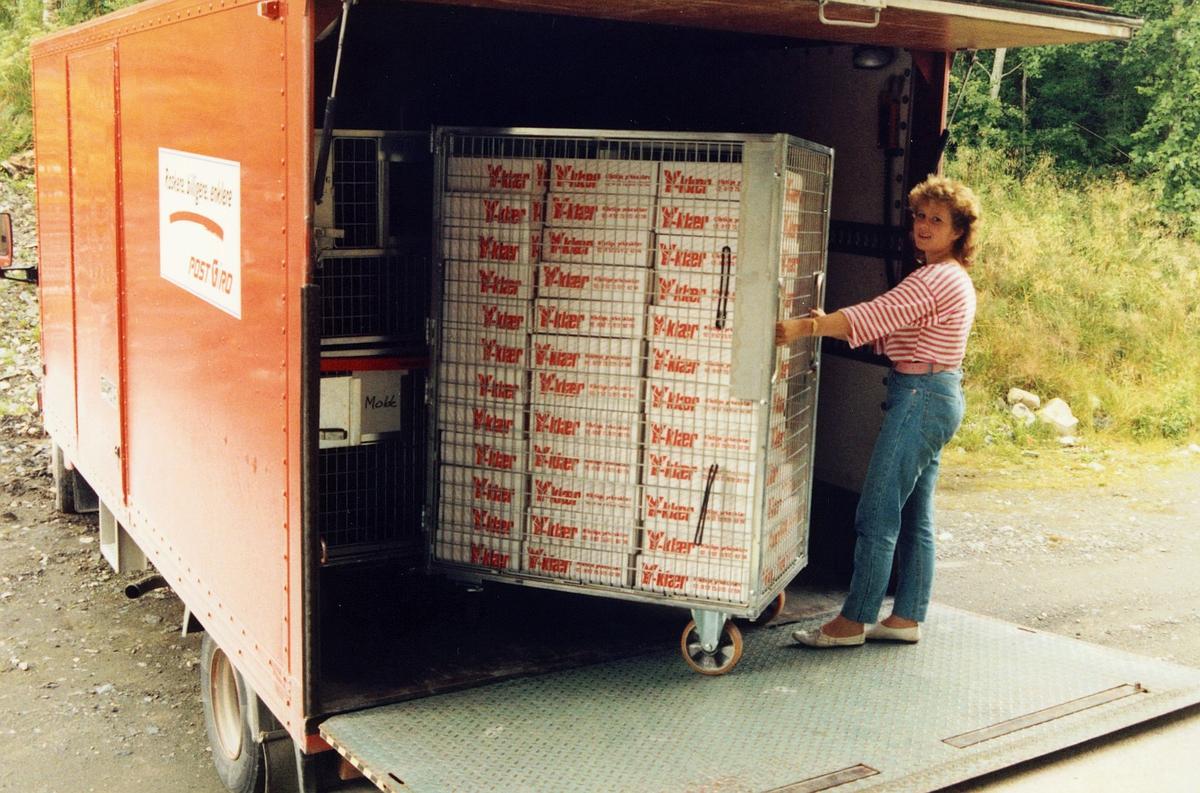 uniform, pakking av Postens profilklær, triller en full container inn i lastebilen