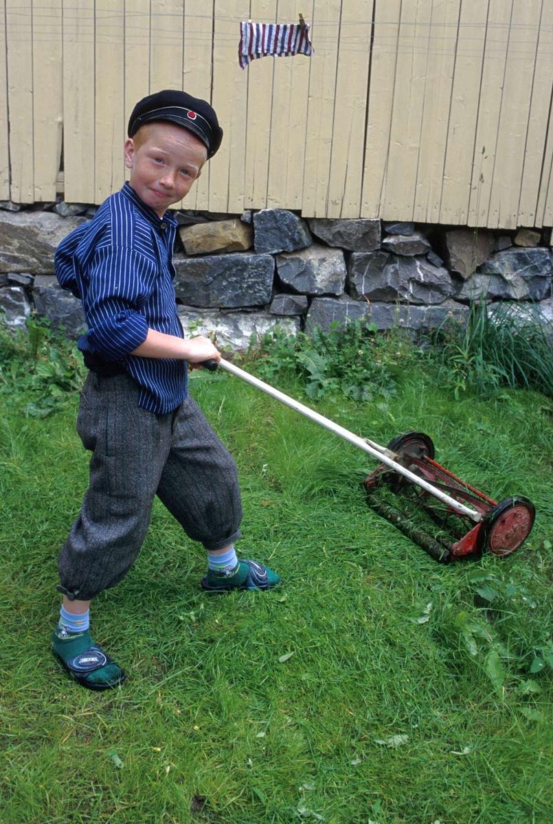 Olsengården, bysamlinga på Maihaugen. Gutt klipper graset i kjøkkenhagen.