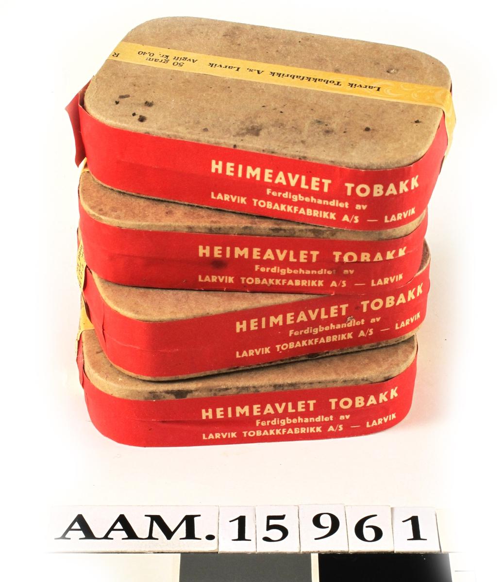 """Heimeavlet tobakk,  4 pakker. Gjerstad.  Grå pappesker, avrundede hjørner, rødt papir  rundt sidene, tvers over gult bånd med tekst:     Larvik Tobakkfabrikk A. S, Larvik.   50 gram Avgift   kr. 0,40. Røyketobakk.   Verdi pr. 100 gram til og med kr. 4,00.  På det røde bånd:   Heimeavlet tobakk. Ferdigbehandlet av Larvik Tobakkfabrikk A/S   Larvik."""""""