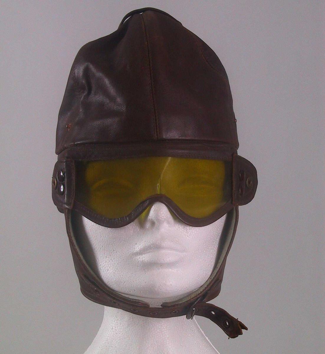 Teknikk: Skinnlue m.gule, nedfellbare plastbriller. For av bomull, trykknapper av messing, åpning v. ørene, spenne for feste under haken. Form: Rund lue m. nakkestykke.