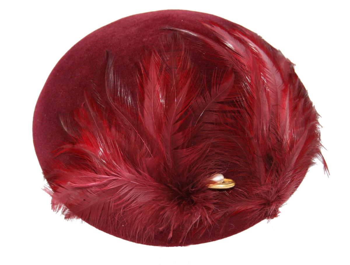 Rund, liten hatt, pyntet med fjær, hattenål til å feste bak på hodet. Smal strikk til å feste under haka.