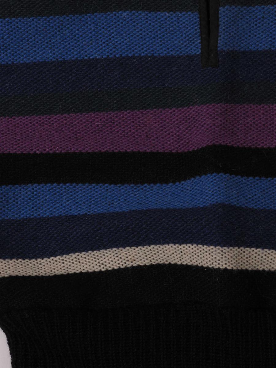Vevd vest med bredt strikket stykke i livet.  Kantet med bendelbånd og knytting i sidene under armene.  Rund hals ned kort splitt foran.   Bendelbånd og strikket parti i sort.  Vevnaden er i sorte, grå, lyseblå, mørkeblå lilla og hvite striper på sort renning.