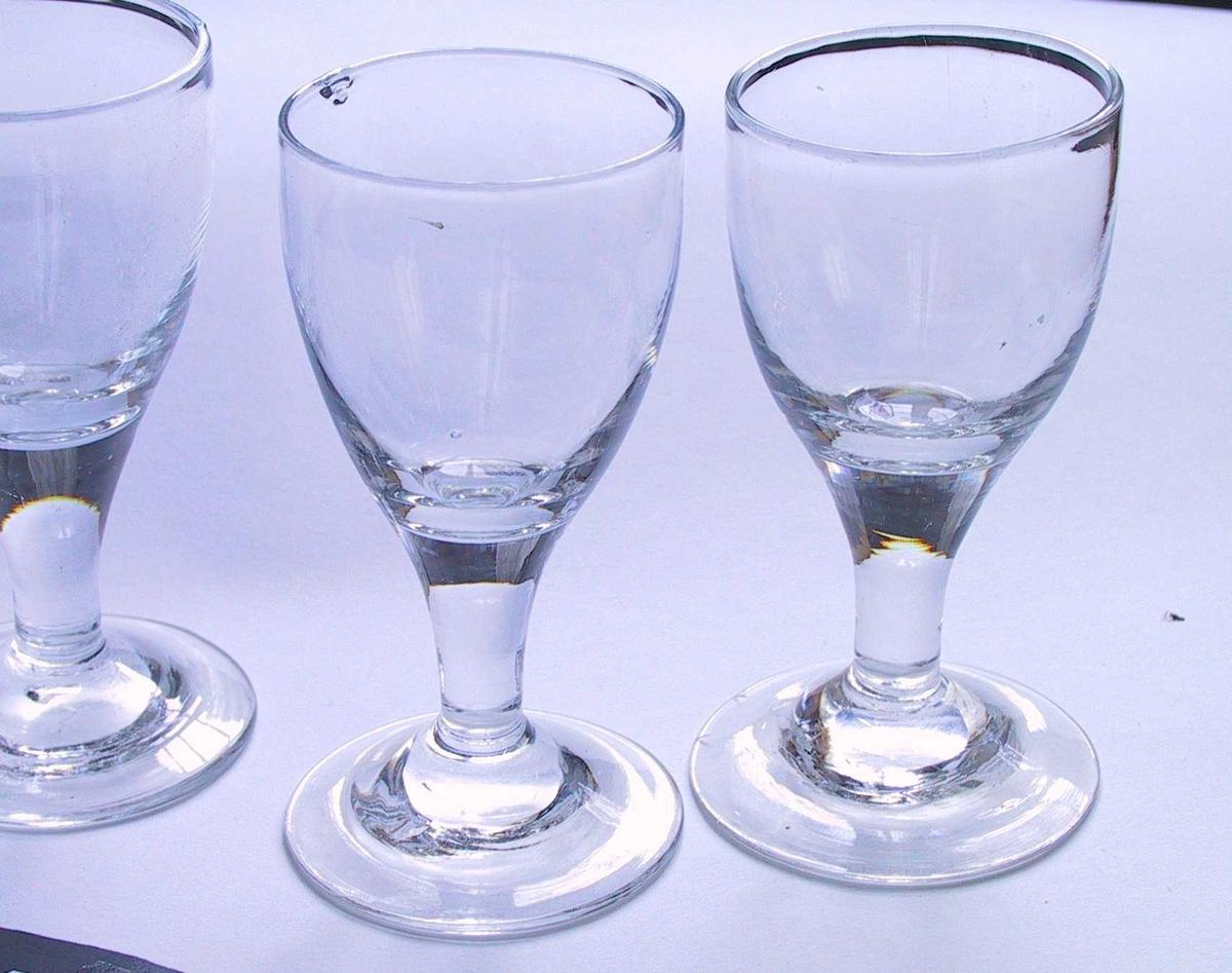 AAM M.0616a-h.  Vinglass, 9 stk., begynnelsen av 1800-tallet.  Glass, svakt grålig. Rund glatt fot, glatt stett som vider seg ut og går jevnt over i cupa, som har svakt buede sider.  a) H. 11,3. Di. fot 6. Di. m 5,5. b) H. 11,5. Diam. fot 6,1. Diam. munning 5,6. c) H. 11,3. Diam. fot 6. Diam. munning 5,5. d) H. 11,2. Diam. fot 6,3. Diam. munning 5,6. e} H. 10,9. Diam. fot 5,9. Diam. munning 5,2. f) H. 11,l. Diam. fot 6,3. Diam. munning 5,5. g) H. 11,3. Diam. fot 5,7. Diam. munning 5,5. h) H. 11,3. Diam. fot 6. Diam. munn 5,4. Tilstand: c) en boble like i kanten. d) 4 små bobler i k. f) 3 små stekk i fotens k.
