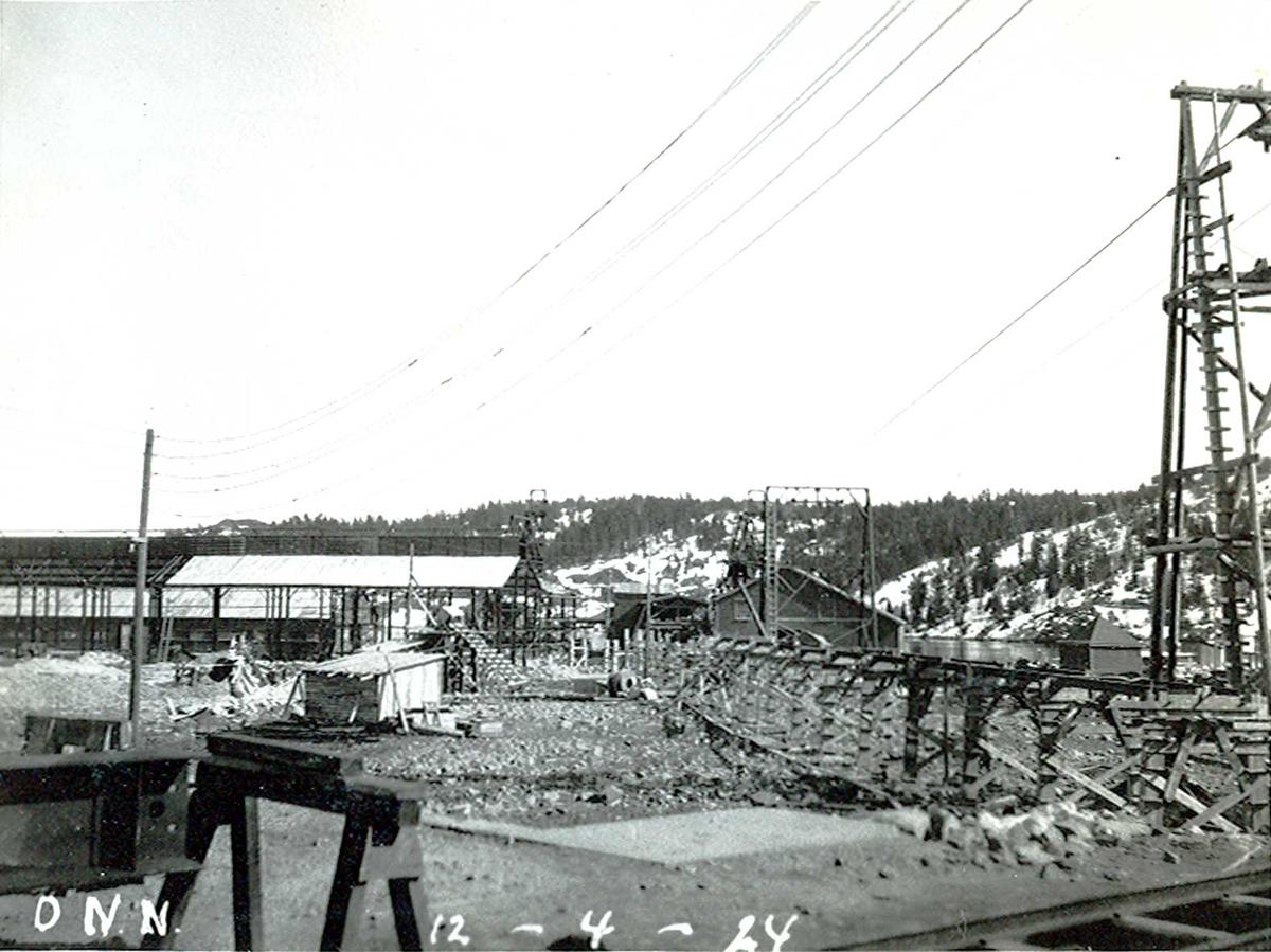 """""""12/04-1924"""" Nitriden. Stekeribygning for steking av elektrodekull til venstre. Videre til høyre kraner på kai, lagerbygning for bauxitt. """"Høybanen"""", skinneanlegg for intern transport for traller med dieseldrevet lokomotiv. Helt til høyre taubanemast. Tromøysund og Tromøy i bakgrunnen."""