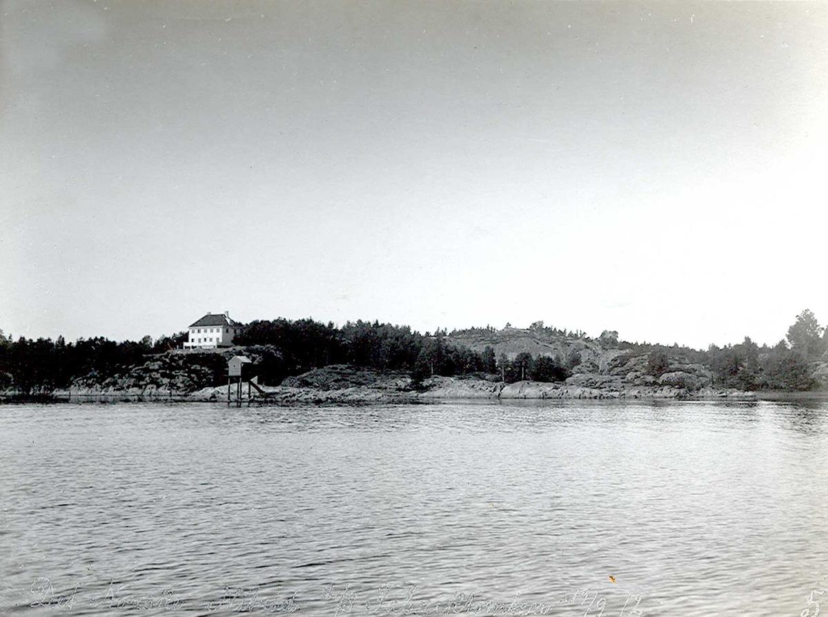 """""""19/09-1912"""" Nitriden. Til venstre Smelteverkets første direktørbolig. Fyrlykt nr. 612 i Norsk Fyrliste, bygget 1894, flyttet til Friisøy lenger vest i 1929. På høyden i bakgrunnen trykkbasseng for vann til bedriftene. Fabrikktomten. Tromøysund i forgrunnen."""