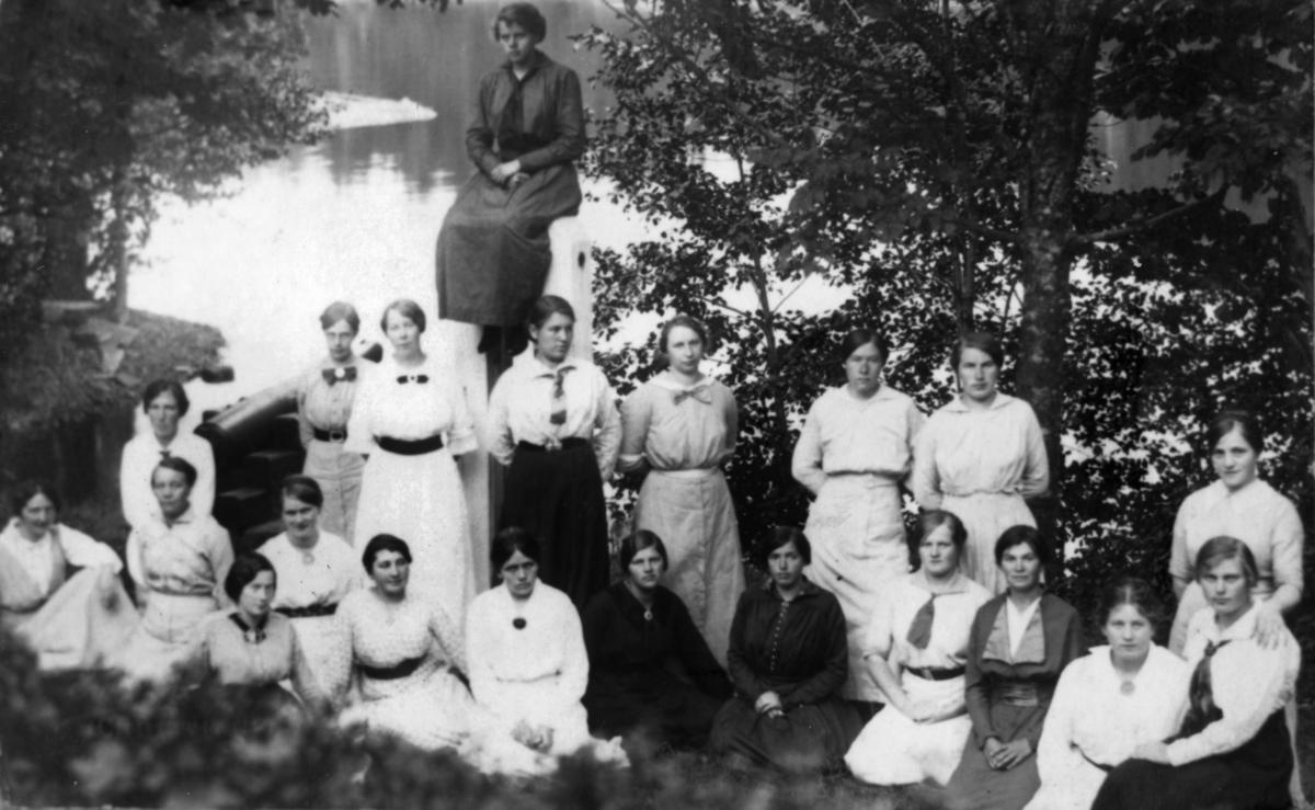 Husmorskolen Egeland Verk. Kvinne nummer tre fra venstre i helt fremste rekke  ( med mørk brosje og hvit kjole) er Kari Grindland (1890-1977), frå Finsland. Ho var håndarbeidslærarinne ved Husmorskolen på Egeland Verk i 1917. Skulen ble nedlagd i 1926.