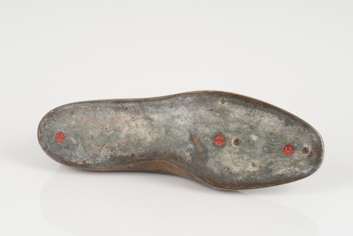 En tremodell i to deler; lest og opplest/overlest (kile) Høyrefot i skostørrelse 45. Hælstykket av metall. Lestekam av skinn.