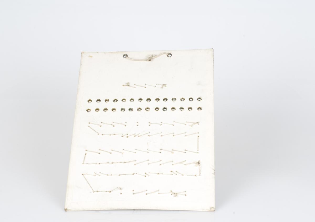 En prøveplate med forskjellige typer maljer påfestet på platen. Maljene er av jern og messing Antall melajer på platen er 85. Påført tekst på platen.