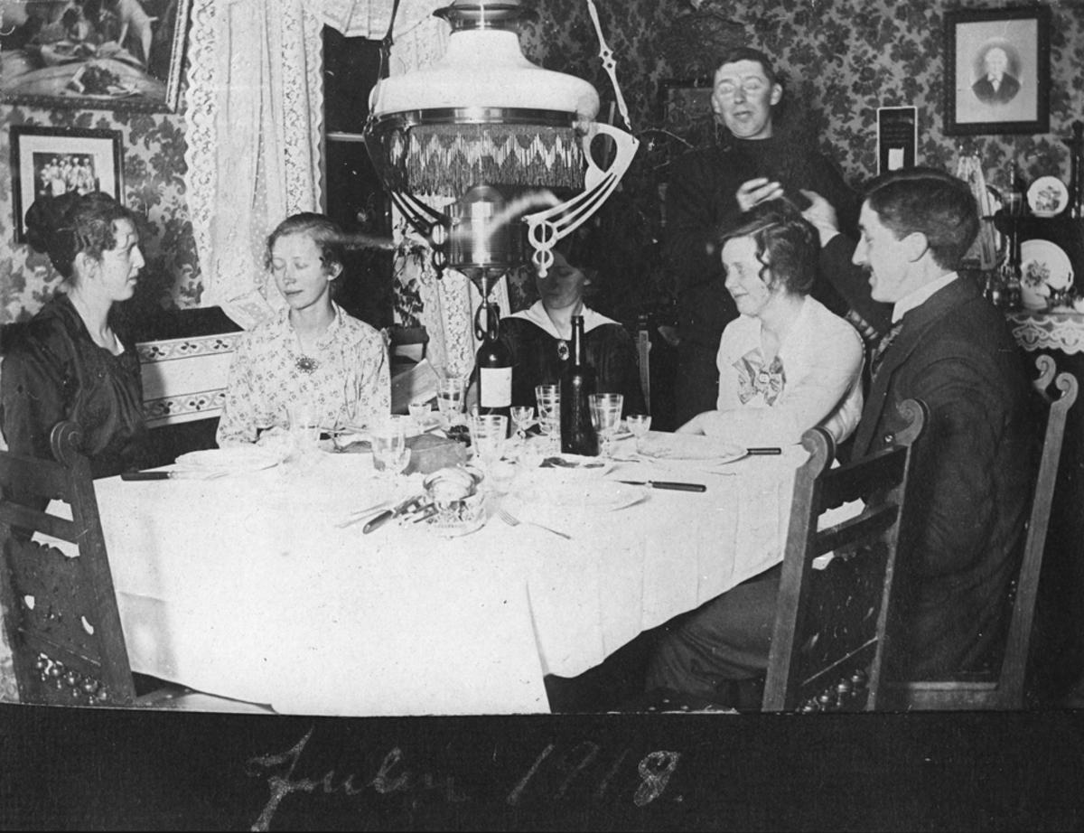 Julen 1918. Kvinner og menn samlet rundt oppdekket middagsbord.